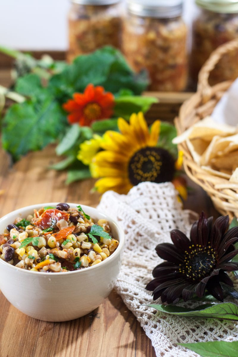 Corn and Black bean salsa in beige bowl surrounded by sunflowers