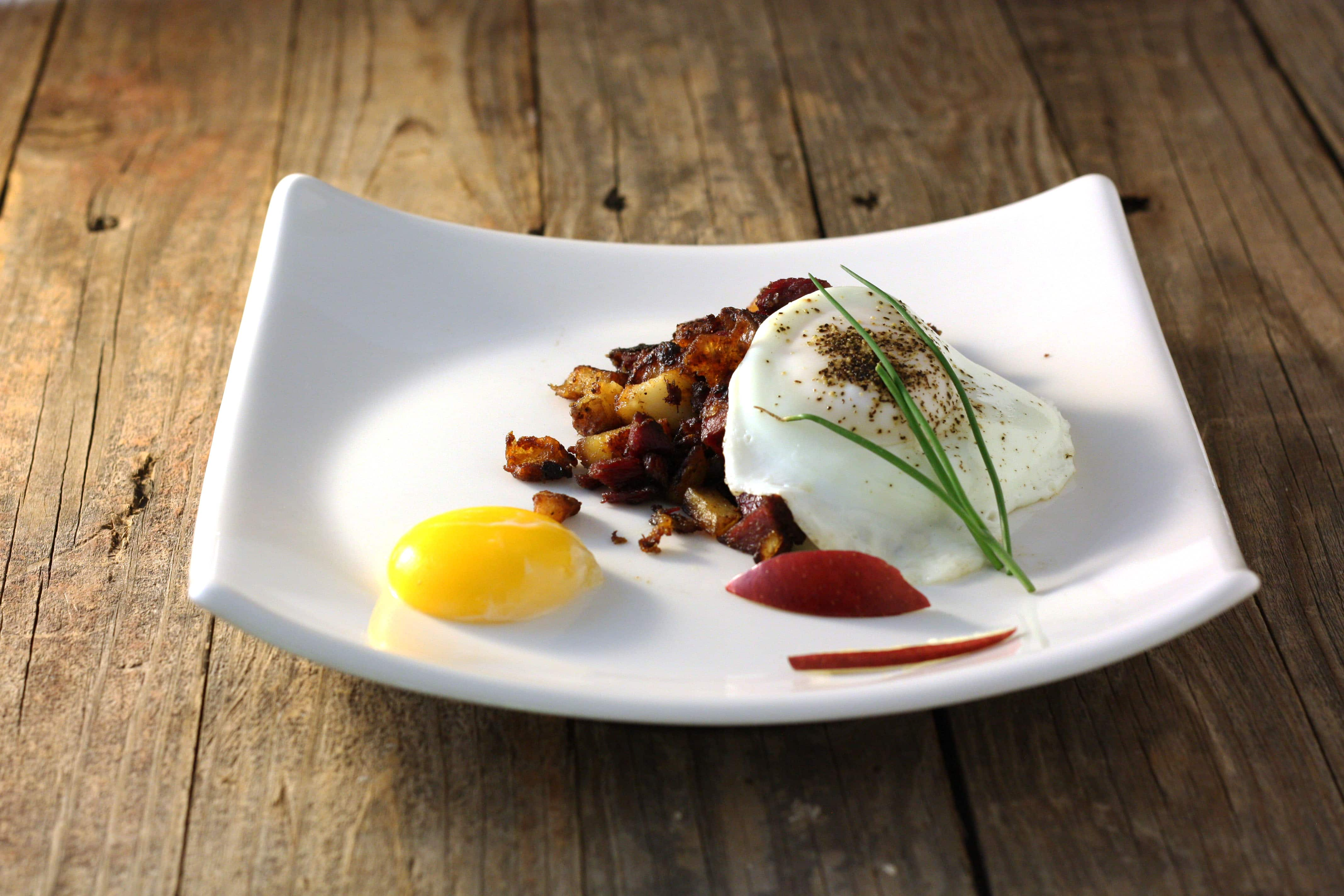 Corned Venison and potato hash topped with egg on white plate