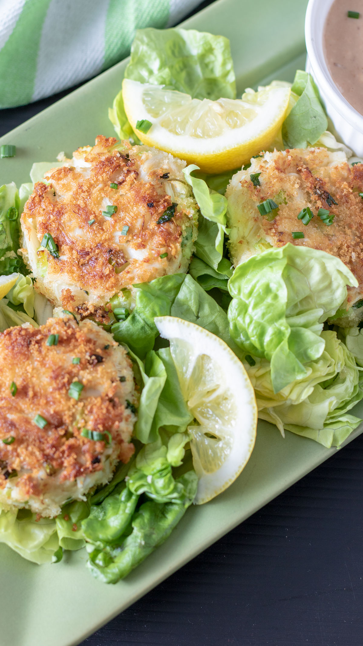 Crab cakes on serving tray with bowl of comeback sauce.