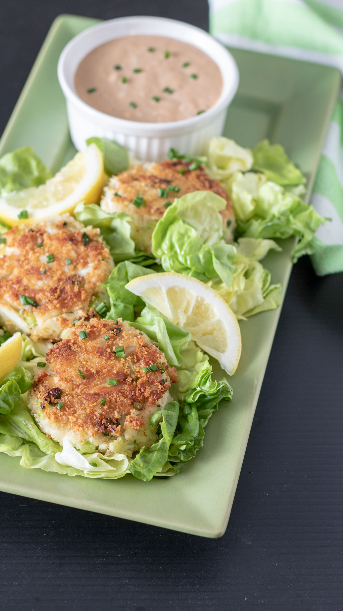 crab cakes and lemons with sauce on serving tray.