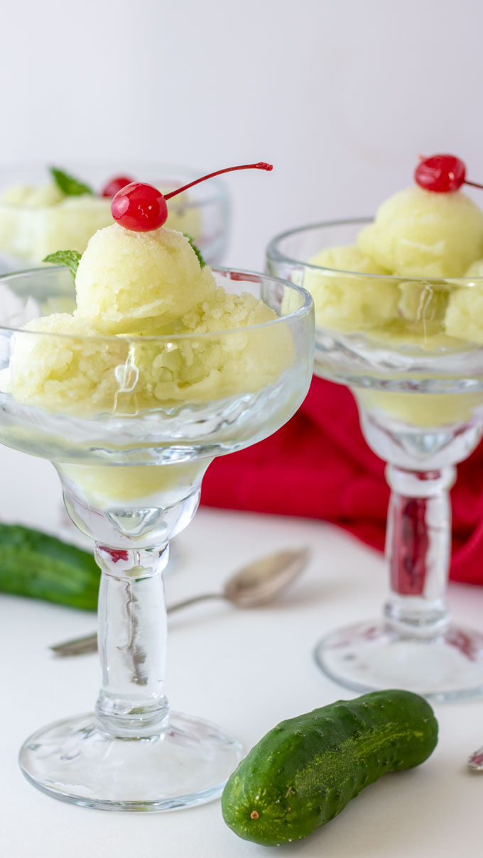 cucumber sorbet in 3 glasses topped with cherry with red napkin and cucumbers.
