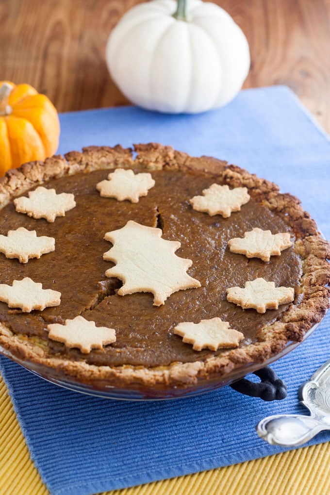 whole dairy free pumpkin pie on blue and yellow mats