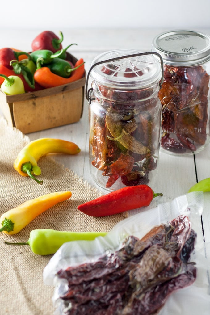 dried pepprs packed in jars and vacuum packed on burlap background