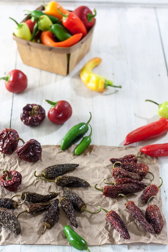 Dried and colorful fresh peppers on white background