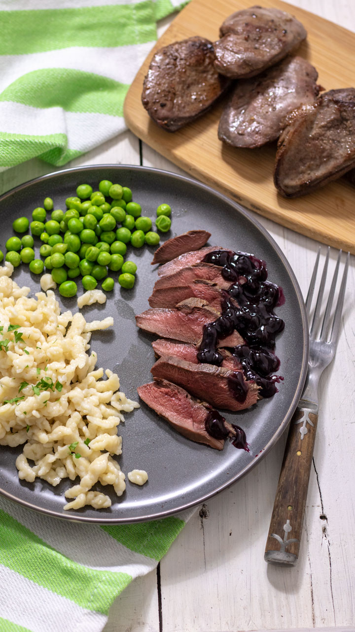 Thinly slice duck breasts with noodles and peas on gray plate.