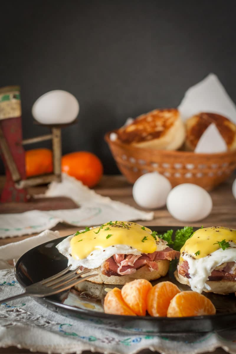 eggs benedict on black plate with parsley garnish