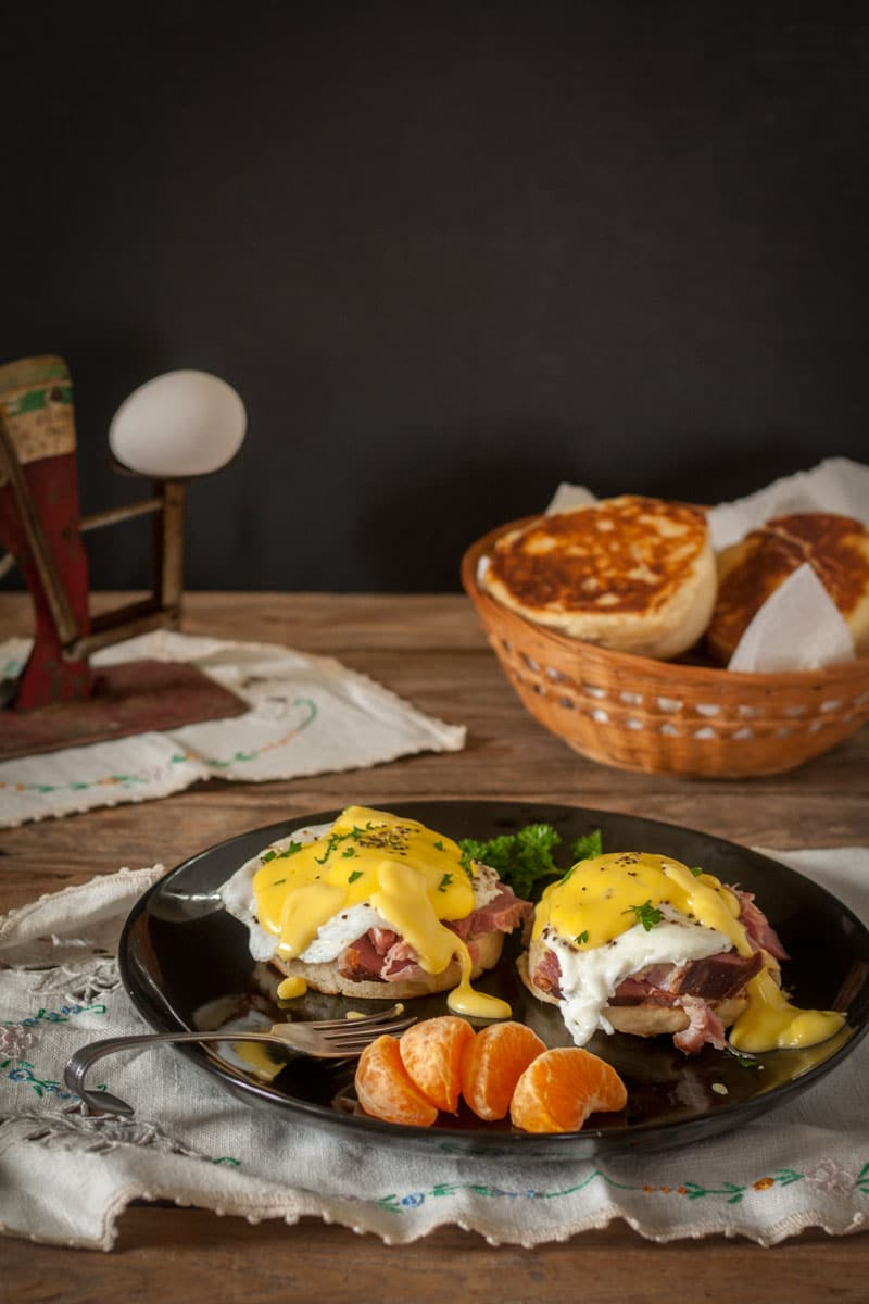 eggs benedict on black plate with antique egg scale in background