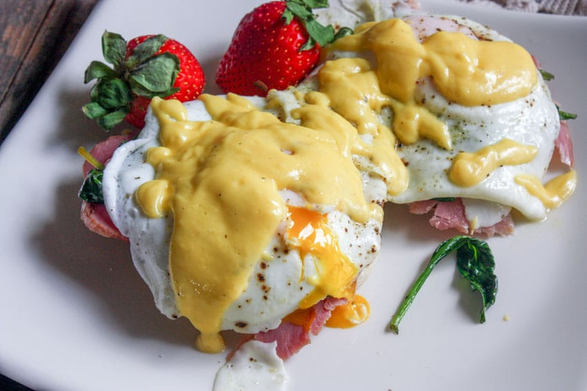eggs benedict on white plate with strawberry garnish with broken yolk
