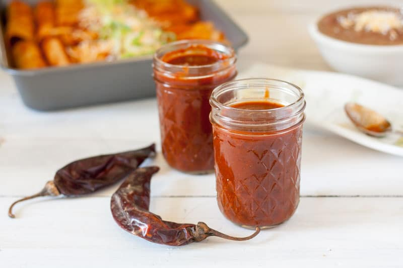 jar of red enchilada sauce with spoon