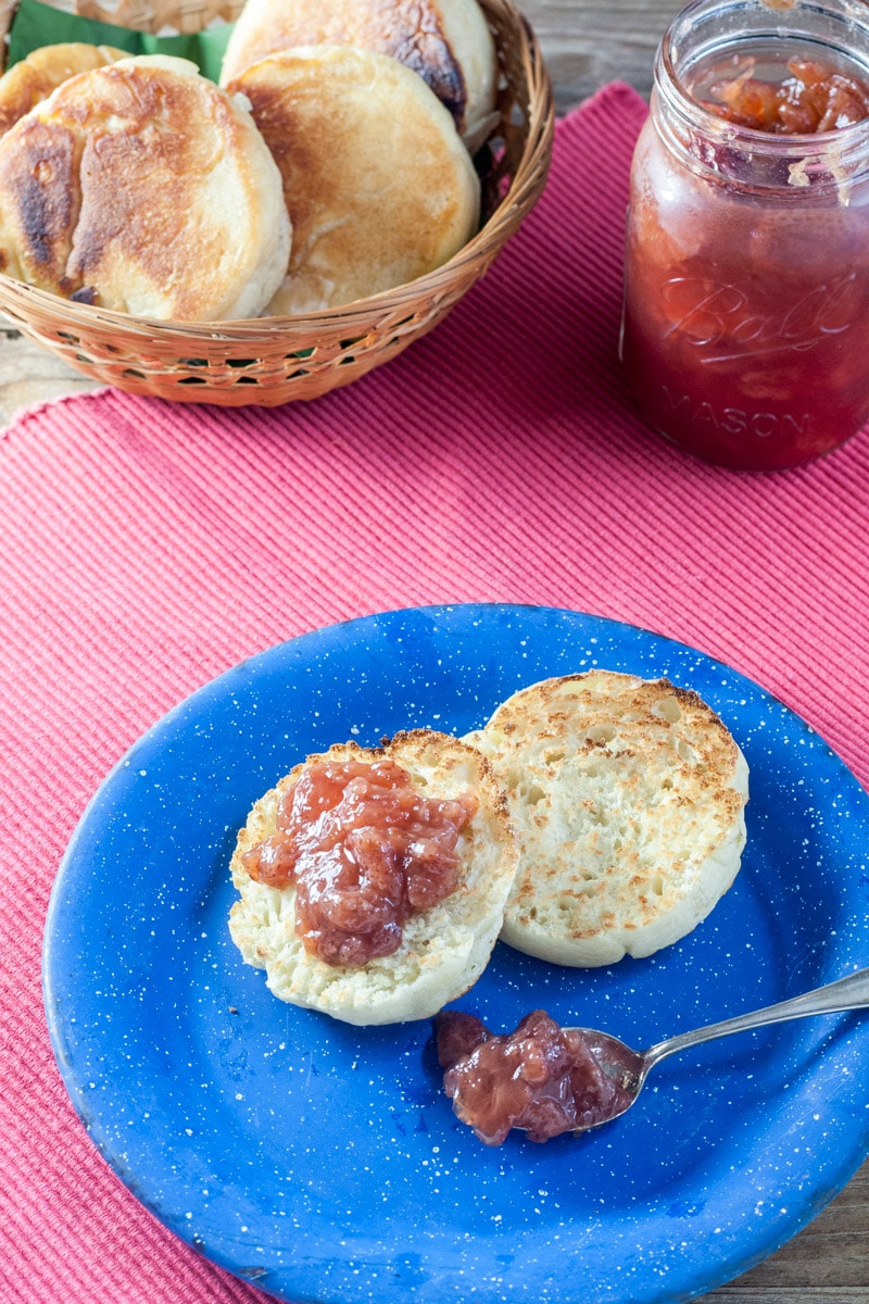 English muffin with strawberry jam on blue pewter plate