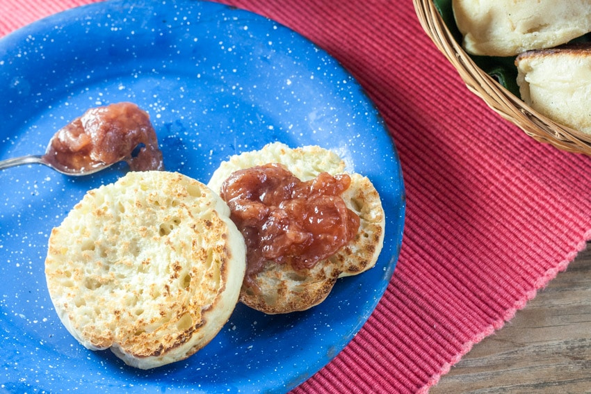 Toasted english muffin and silver spoon of jam on blue plate