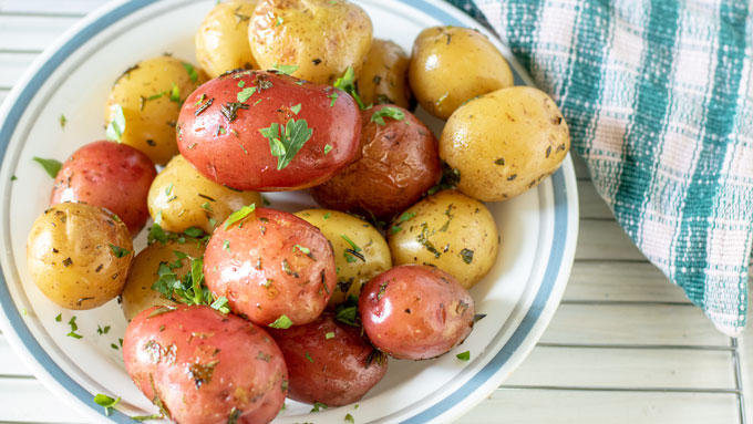 Grilled potatoes with fresh herbs on top.