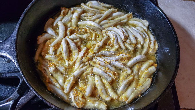 Breaded smelt in cast iron pan.