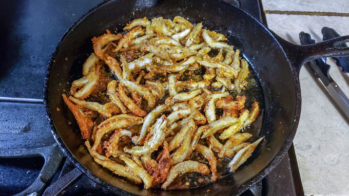 Crispy smelt cooking in cast iron pan.