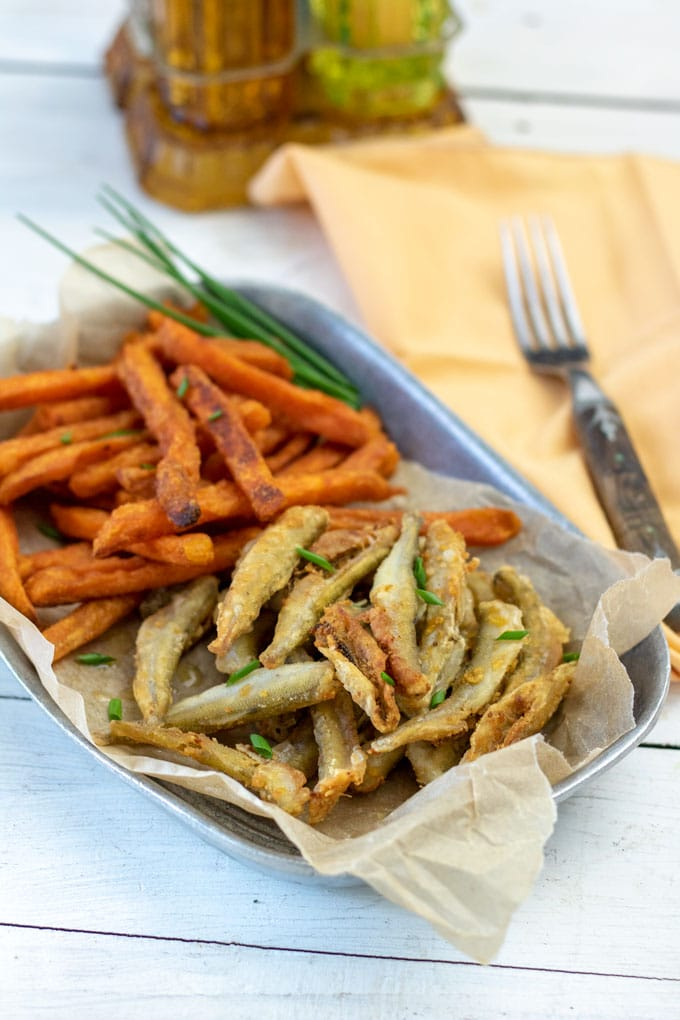 smelt with sweet potatoes on pewter bowl
