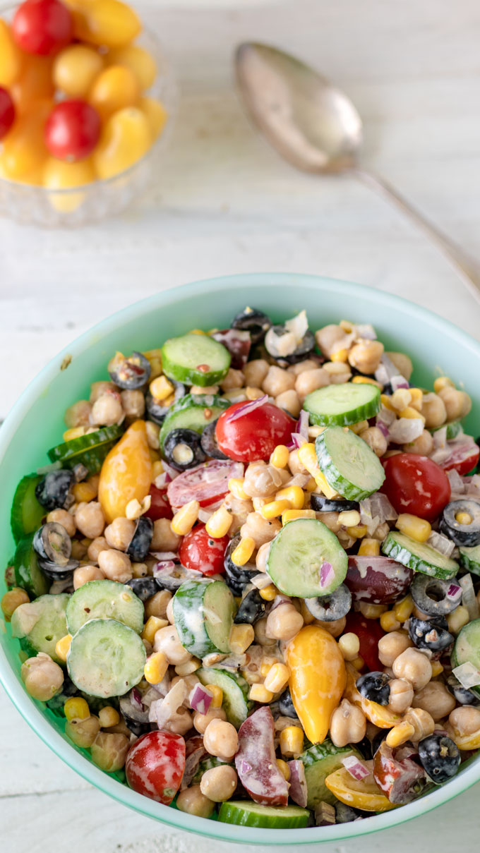 Colorful garbanzo bean salad in antique green bowl
