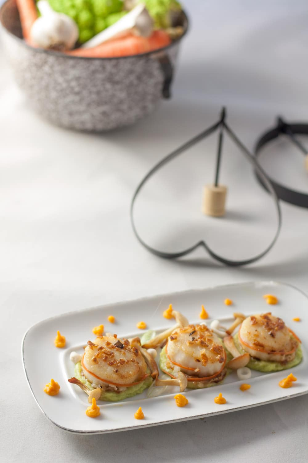 garlic seared scallops on white plate with romanesco and carrot puree