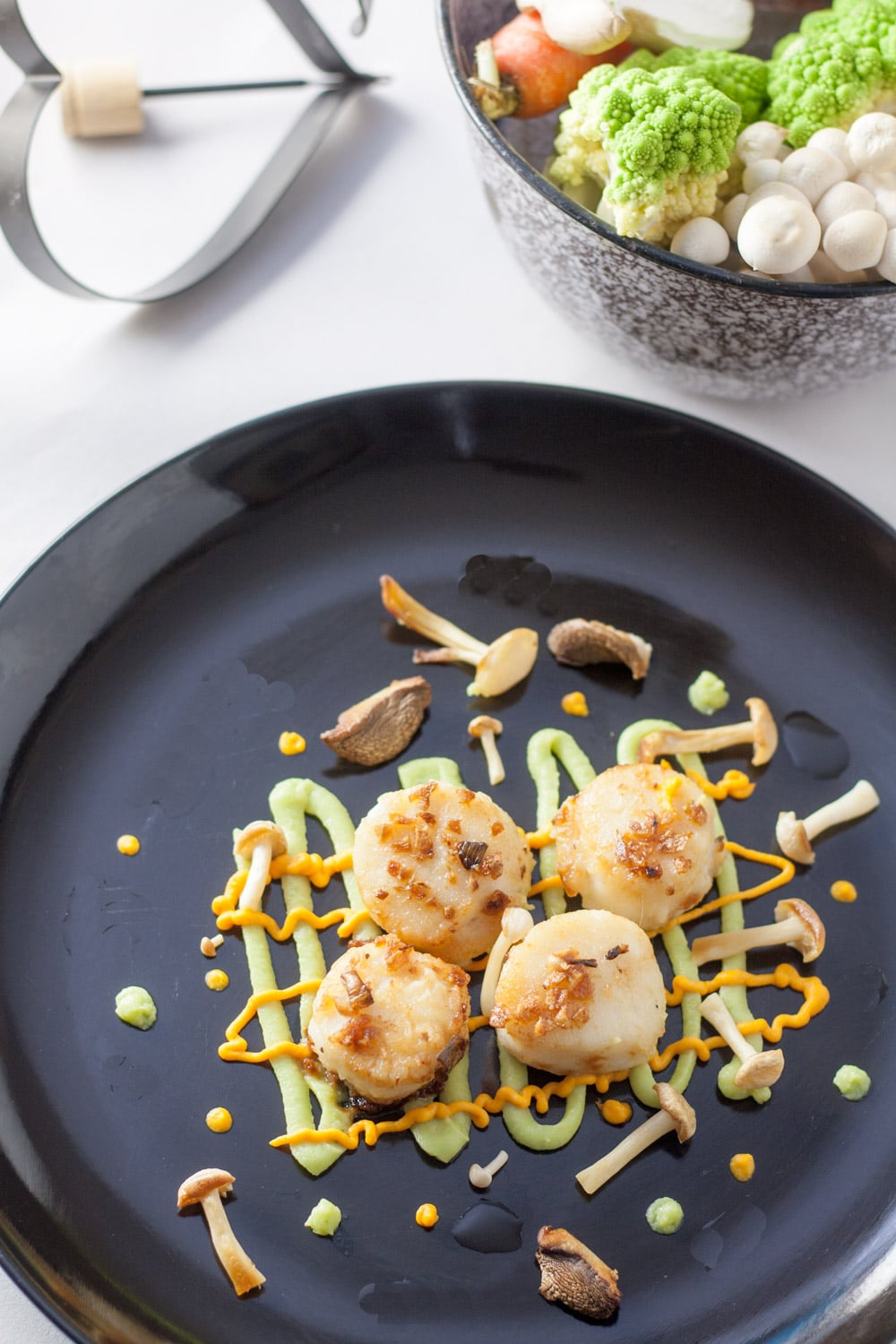 garlic sea scallops on black plate with romanesco and carrot purees