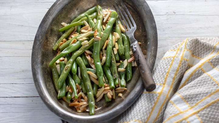 Sauteed green beans and almonds on silver dish with wooden spoon.