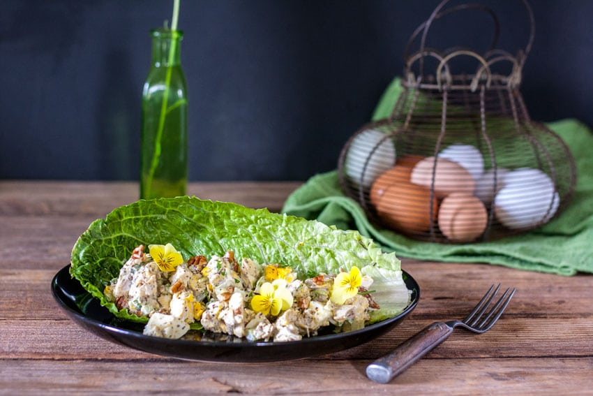 grilled chicken salad with large chunks of pecans and eggs, served on large lettuce leaf garnished with edible yellow pansies
