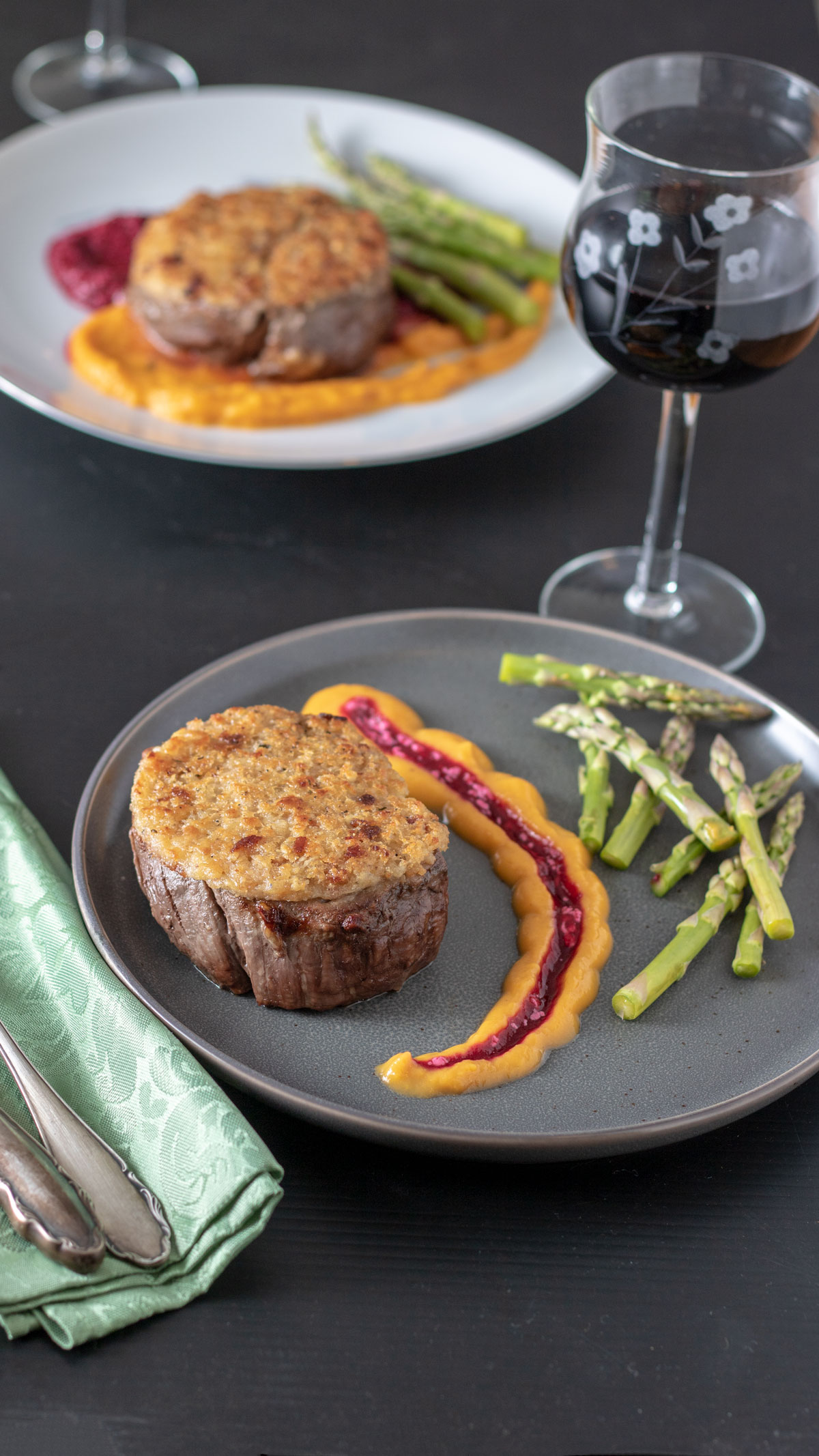 Horseradish crusted beef filet on gray plate with scond dish in background.