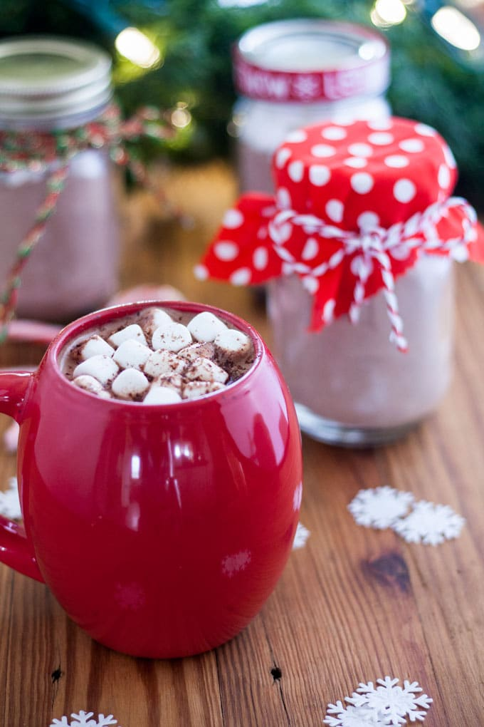 Large red mug filled with hot cocoa topped with marshmallows and shaved chocolate