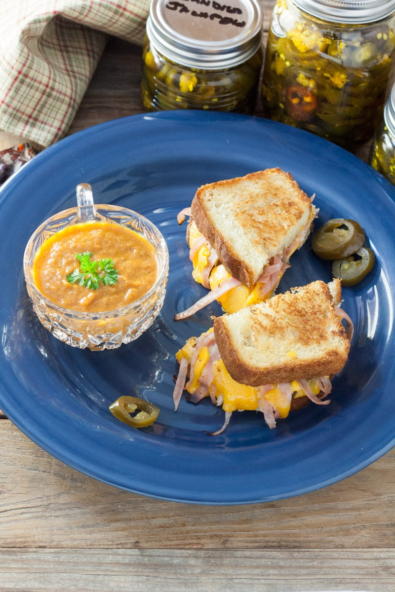 Jalapeno Grilled Cheese Sandwaich on a blue plate with a cup of carrot soup