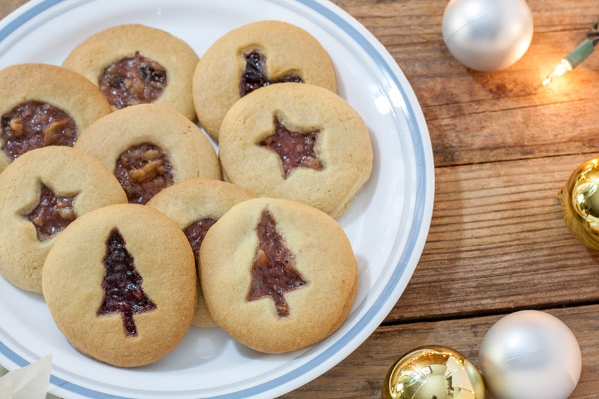 Jam filled cookies on white plate with Christmas Tree cutout, star cutout and circle cut out