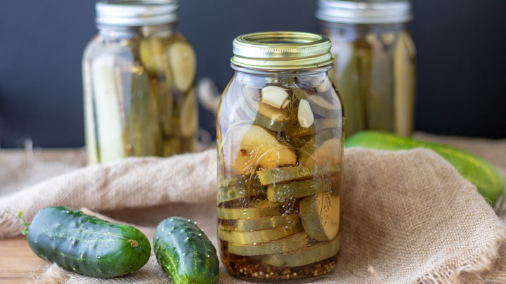 pickles in jars with fresh cucumbers in photo
