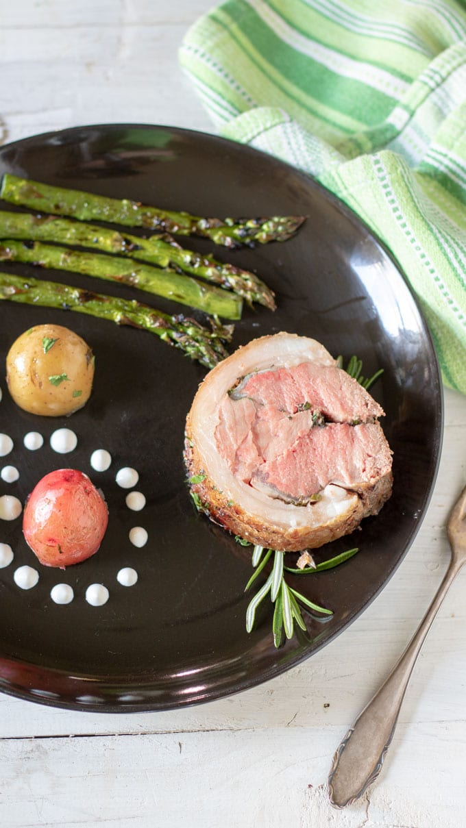 slice of lamb on black palte with potatoes and asparagus