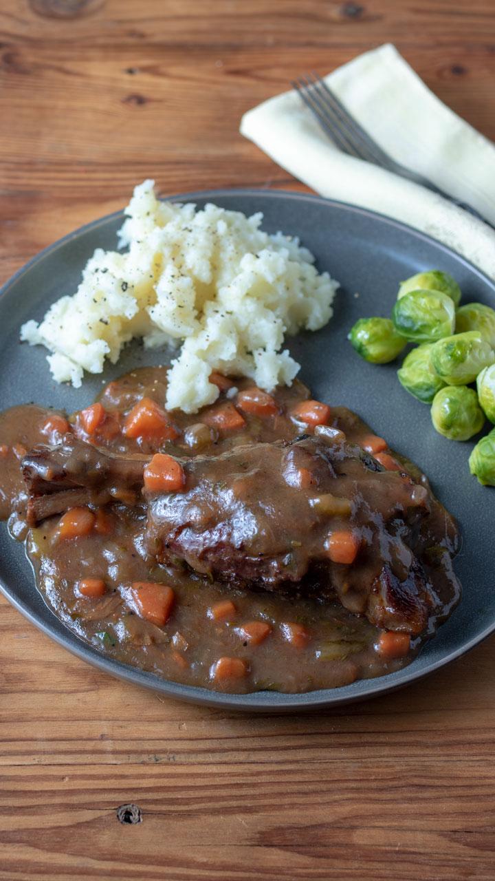 lamb shank dinner on gray plate.