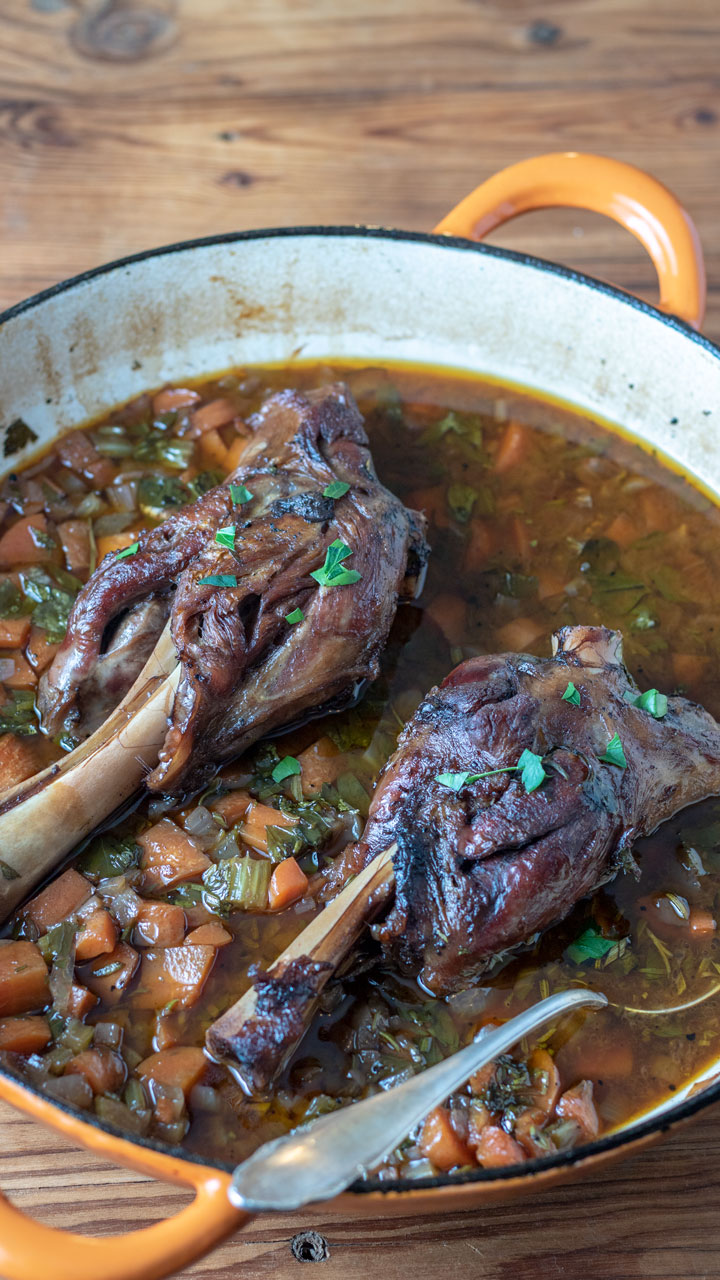 Lamb shanks with sauce in skillet.