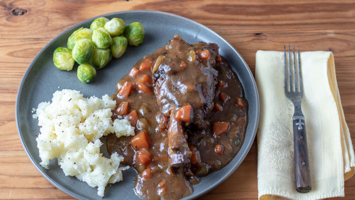 Lamb shank with mashed potatoes and vegetables.