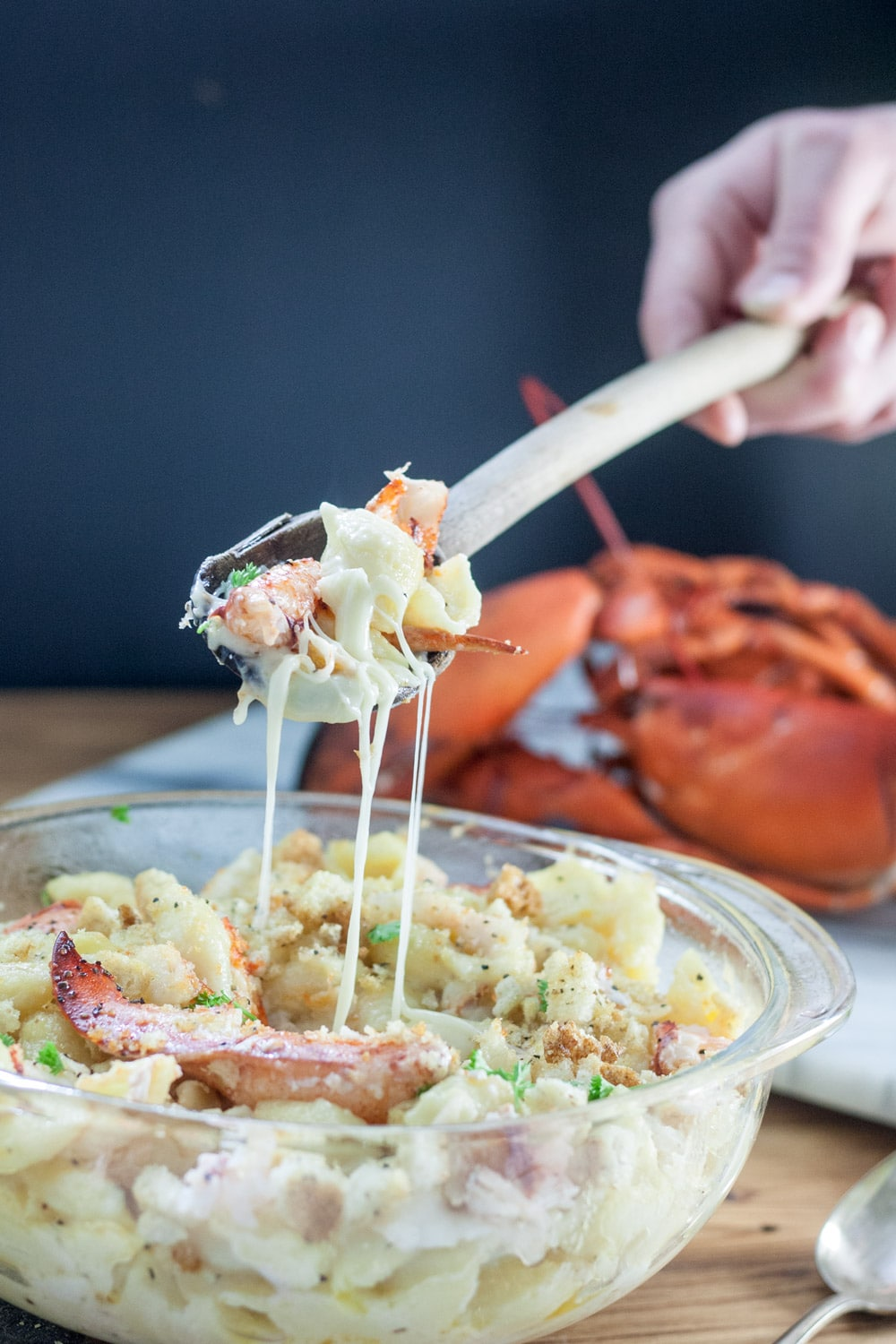 lobster mac and cheese on spoon, dripping with cheese