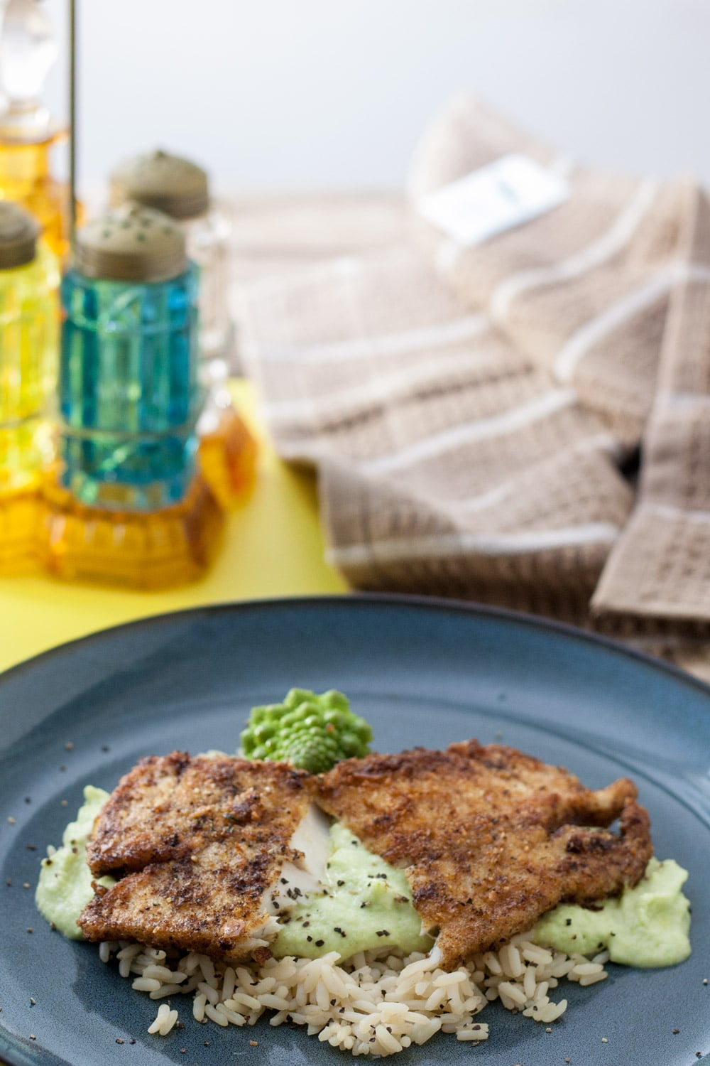 pike fillet on blue plate served with Romanesco puree and rice
