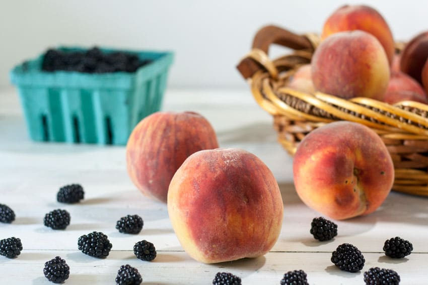 peaches and blackberries on white board