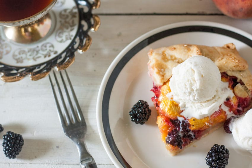 Piece of blackberry peach galette on on white plate with black rim, topped with a scoop of ice cream.