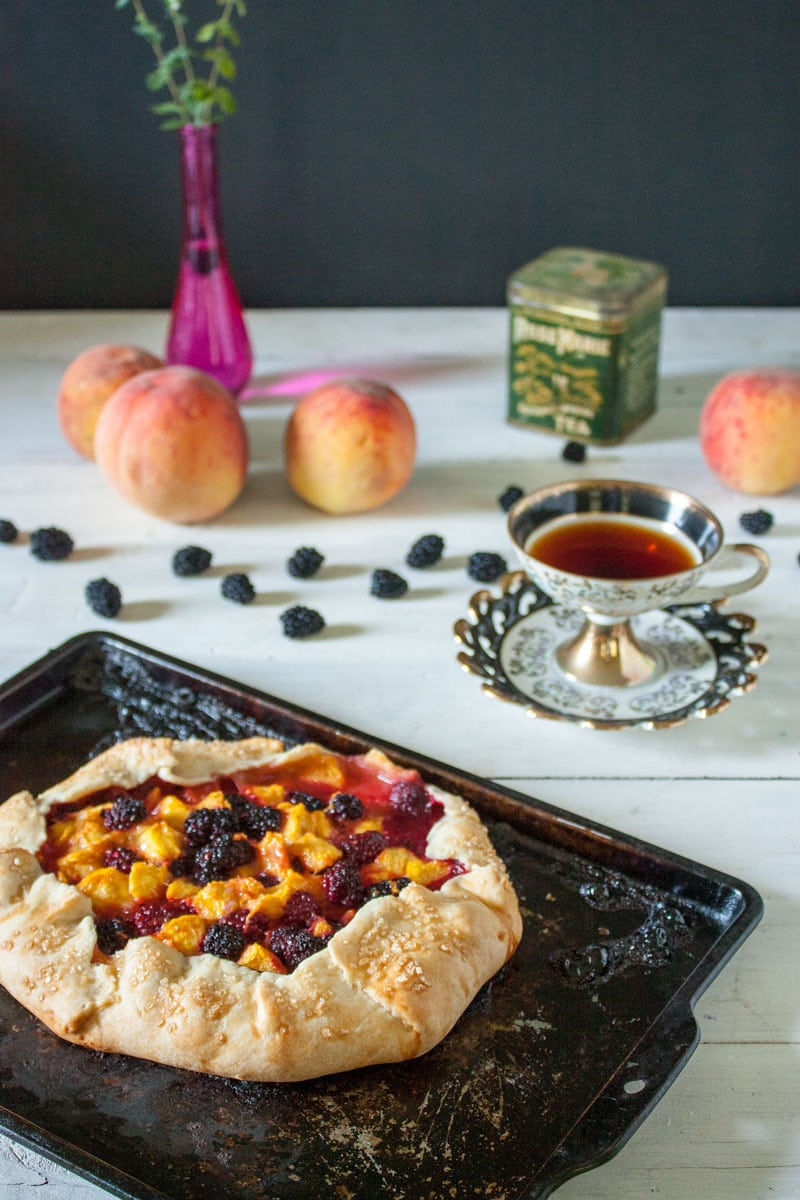 whole peach galette on antique baking tray