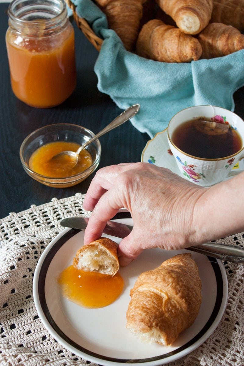 hand grabbing piece of croissant with low sugar peach jam