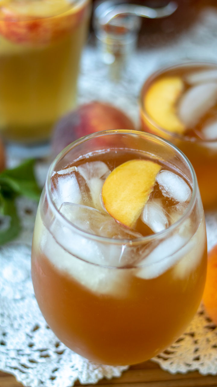 Glass filled with peach tea and garnished with peaches.