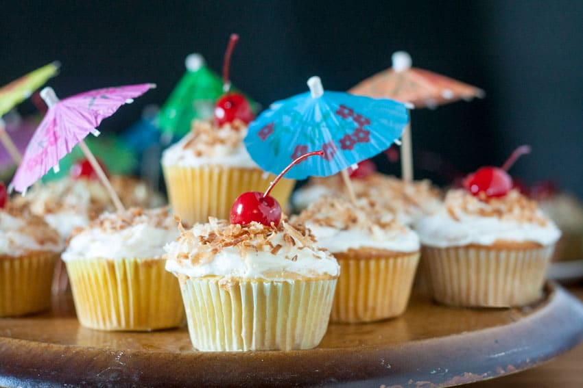 close up of pina colada cupcake with cherry on top and drink umbrellas