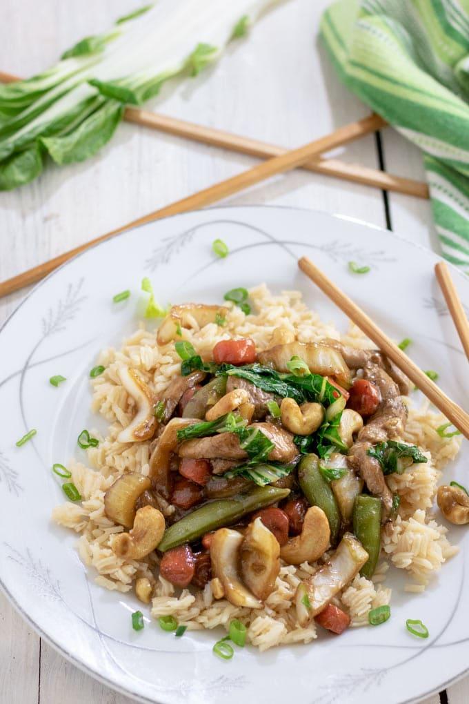 Cashew pork stir fry on white plate with chopsticks