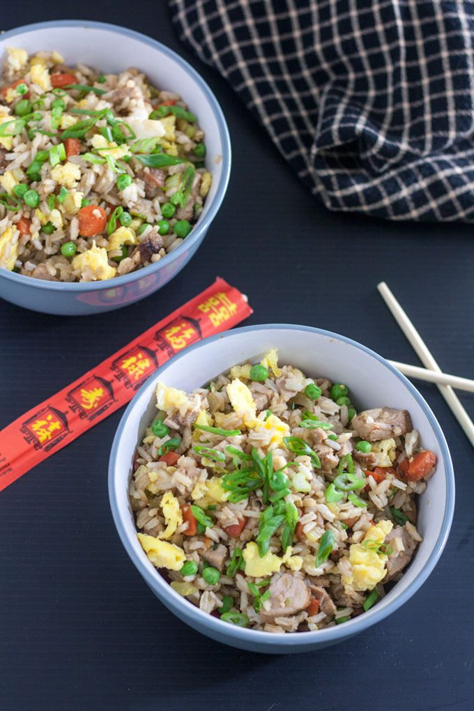 pork fried rice in 2 white bowls with chopsticks