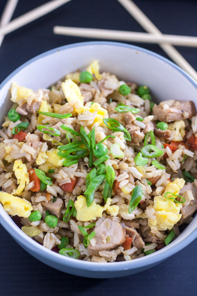close up of pork fried rice with eggs, peas and carrots