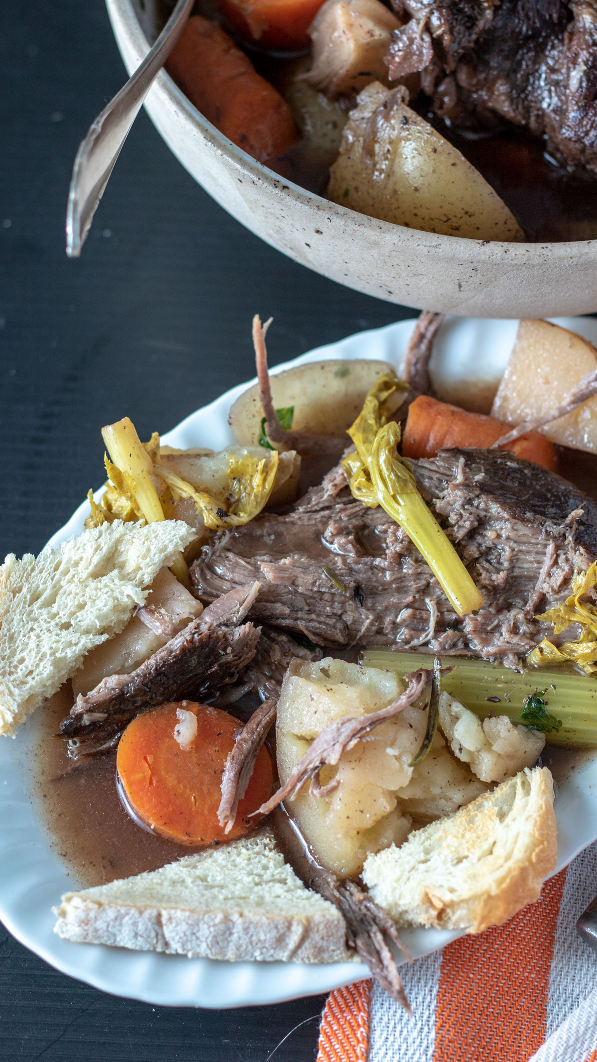 Serving of pot roast on white plate topped with vegetables with toast points.