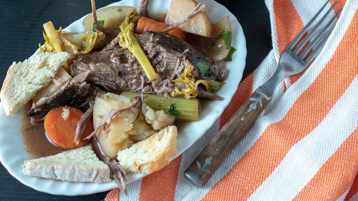 Serving of pot roast on white plate.