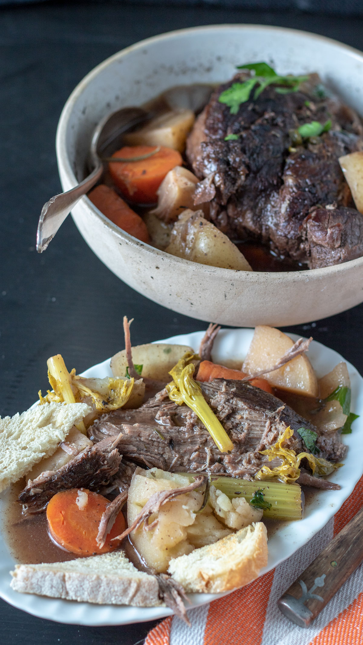 Serving of pot roast on white plate with serving bowl in background.