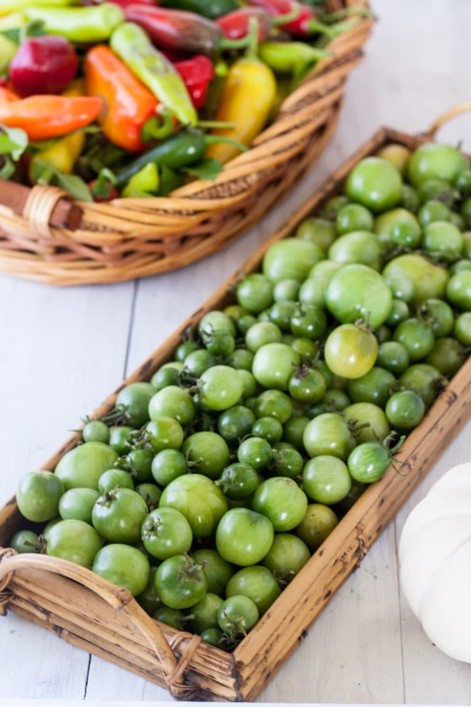 basket of green tomatoes with basket of multicolored peppers