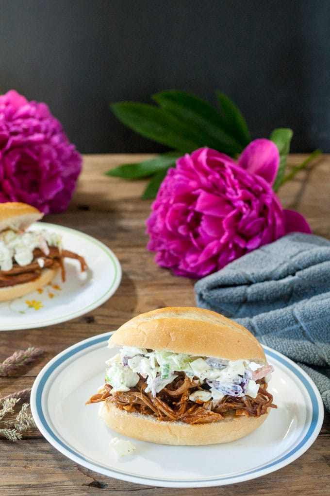 pulled pork sandwiches topped with cole slaw on white plate with blue trim on a barnwood base