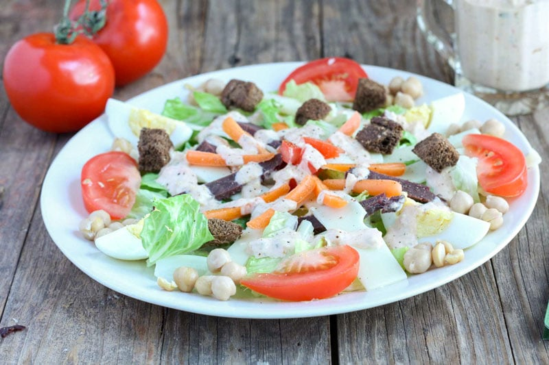 Dinner salad on ehite plate with corned venison, swiss cheese, tomato & boiled egg.